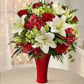 Red roses, carnations, and Peruvian lilies set the back drop for the white Asiatic lilies to pop, arranged amongst green mini hydrangea, bupleurum, and holiday greens, perfectly set in a keepsake