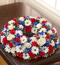 •Comforting table wreath arrangement of red, white and blue blooms such as roses, delphinium, carnations, hypericum, mini carnations and daisy poms, gathered with gypsophilia, variegated pittosporum and seeded eucalyptus •Hand-crafted by our select florists to be sent to the cremation service to honor friends or family members •Also appropriate for smaller memorial services in the home •The cremation urn or a framed photograph can be placed in the center to present a lovely tribute at the service or home