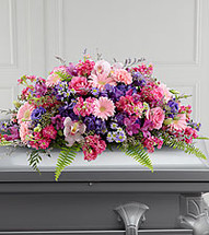 Glorious Garden Casket Spray includes pink carnations, cymbidium orchids and gerbera daisies, hot pink roses and stock, purple hydrangea and lisianthus, lavender alstroemeria, Monte Casino and limonium all accented with lush greens. It''s made to fit over the closed portion of a casket cover during visitation at a funeral home, at a funeral service and at a graveside ceremony at the cemetery.