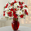 Bouquet includes: red Peruvian Lilies, red mini carnations, white chrysanthemums, white Peruvian Lilies, and lush holiday greens accented with a red vase.