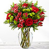 Rich red roses, red carnations, and red Peruvian Lilies are accented perfectly with bright green button poms and a collection of lush Christmas greens to create a stunning seasonal display. Presented in a clear glass vase.