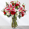 This bouquet brings together rich red roses, stunning Stargazer Lilies, red mini carnations, and white chrysanthemums to create a truly beautiful Christmas flower arrangement. Accented with fragrant and lush Christmas greens and presented in a clear glass vase.