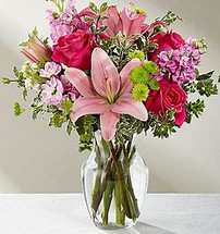 Hot pink roses are bright and beautiful arranged amongst pink Asiatic Lilies, pink gilly flower, green button poms, bupleurum and lush greens to create that perfect gift of flowers. Presented in a clear glass vase