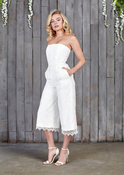 A stunning corseted bridal jumpsuit, which cinches in at the waist giving a beautifully shaped silhouette. The geometric style lace gives a modern take on bridal lace and with the culotte shaped trouser leg this is perfect the fashion forward bride.